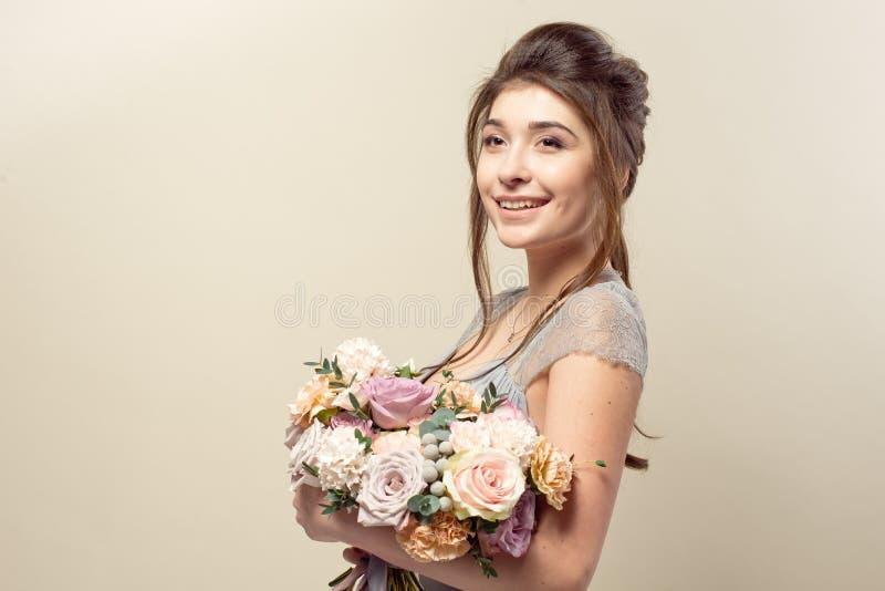 Элегантная девушка со стрижкой в мягких голубых платье и макияже держит букет стильного букета цветков стоковое изображение rf
