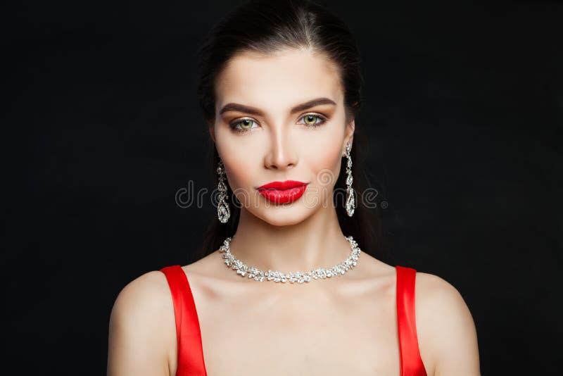 Элегантная женщина брюнета с красным макияжем и бриллиантовым колье губ стоковая фотография rf