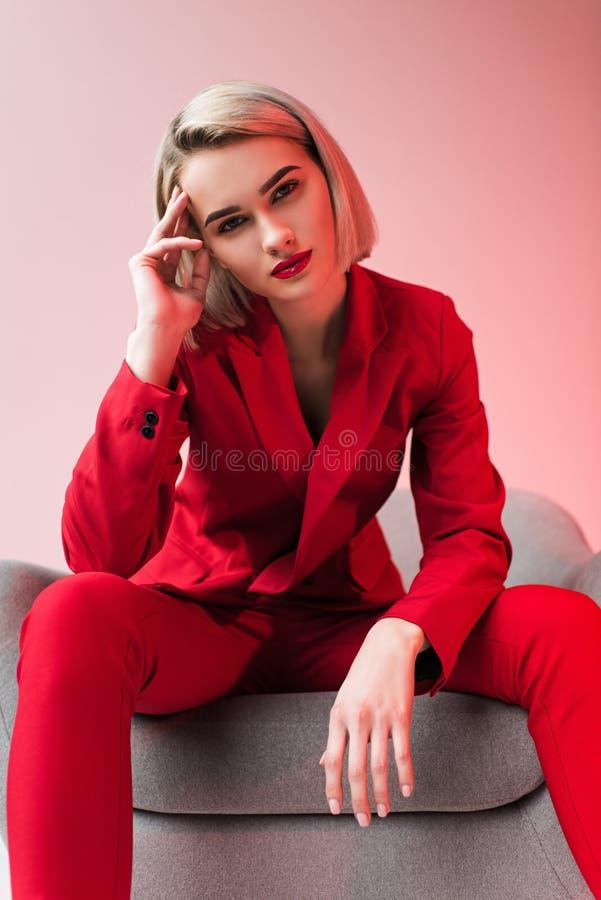 элегантная женщина в красных одеждах представляя в кресле стоковые изображения rf