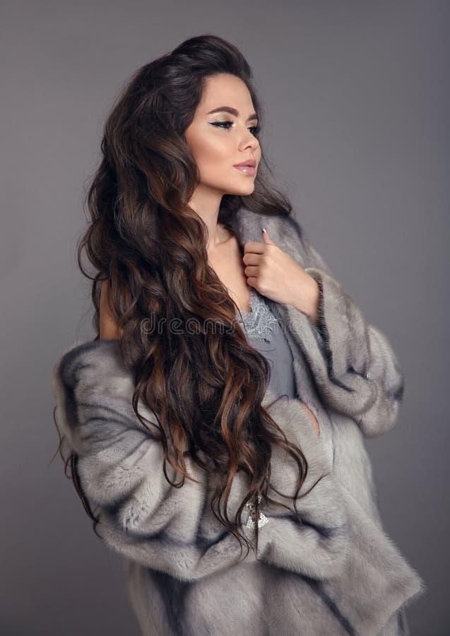 Элегантная женщина в меховой шыбе норки изолированной на серой предпосылке студии Девушка брюнета моды в роскошном outerwear зимы стоковое изображение rf