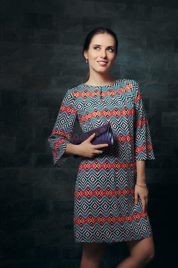 Элегантная женщина в платье коктеиля держа портмоне готовый для партии стоковые изображения rf