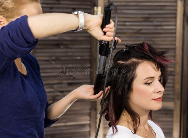 Элегантная женщина в салоне красоты Парикмахер coiffure в форме большой скручиваемости Стиль причёсок свадьбы концепции стоковое изображение