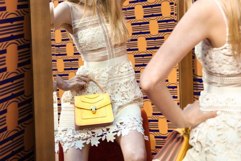 Элегантная женщина держит стильную кожаную сумку представляя нося модное белое платье стоковое фото rf