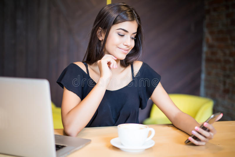 Элегантная женщина улыбки детенышей с портативным компьютером на кафе используя мобильный телефон стоковое фото rf