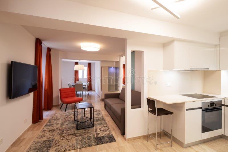 Элегантная живущая комната с красным дизайнерским креслом и современной белой кухней стоковые фотографии rf