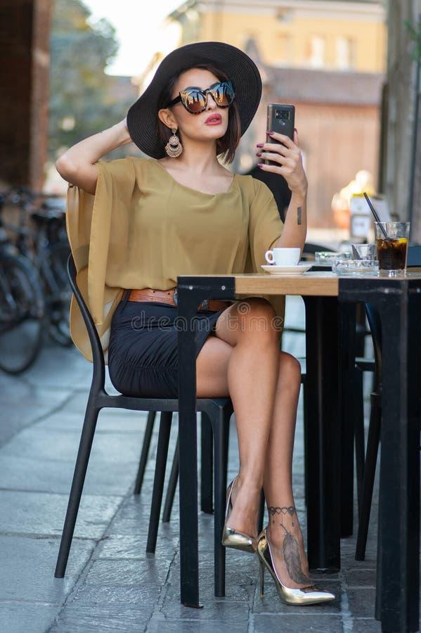 Элегантная итальянская женщина с шляпой и стеклами проверяет ее состав на зеркале ее smartphone стоковая фотография rf