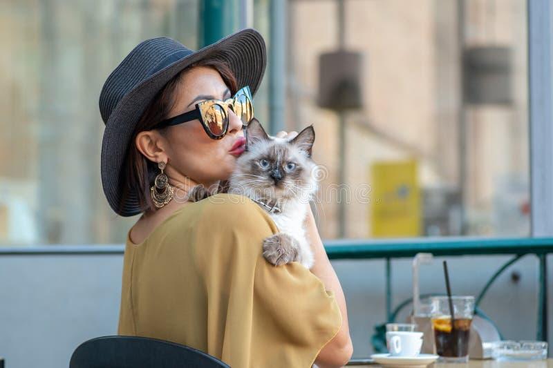 Элегантная итальянская женщина с шляпой и стеклами целует кота стоковые фотографии rf