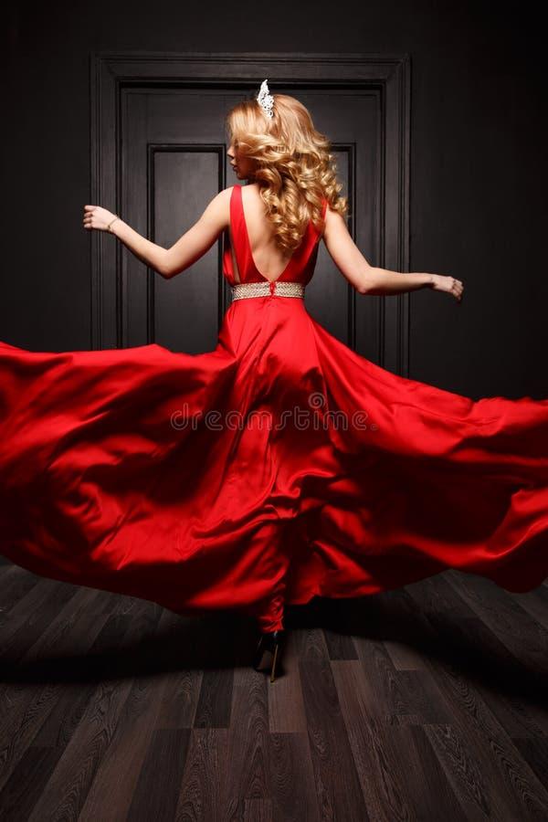 Элегантная и запальчиво женщина с тиарой на ее голове в платье красного вечера порхая захват в движении, закручивая стоковые фотографии rf