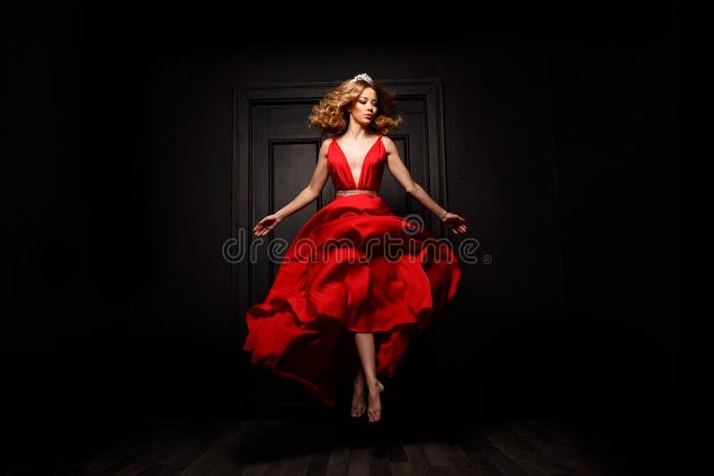 Элегантная и запальчиво женщина с тиарой на ее голове в платье красного вечера порхая захват в движении, над землей стоковые изображения