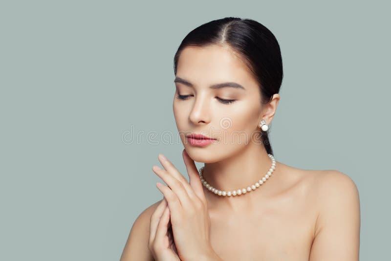 Элегантная модельная женщина с ожерельем жемчугов ясной кожи нося белым стоковая фотография rf