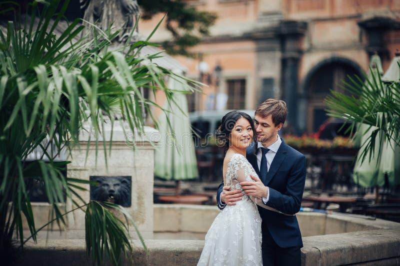 Элегантная невеста при groom идя около старого католического собора стоковые фото