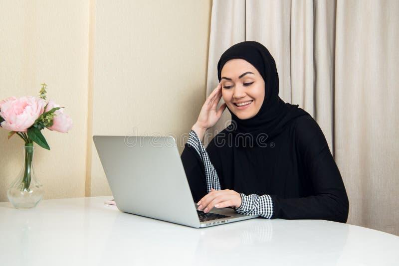 Элегантная привлекательная мусульманская женщина используя мобильный ноутбук ища онлайн ходя по магазинам информацию в живущей ко стоковое фото
