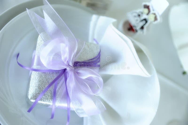 Элегантная установка таблицы с белым фарфором и серебряной коробкой keepsake с фиолетовыми акцентами стоковое фото