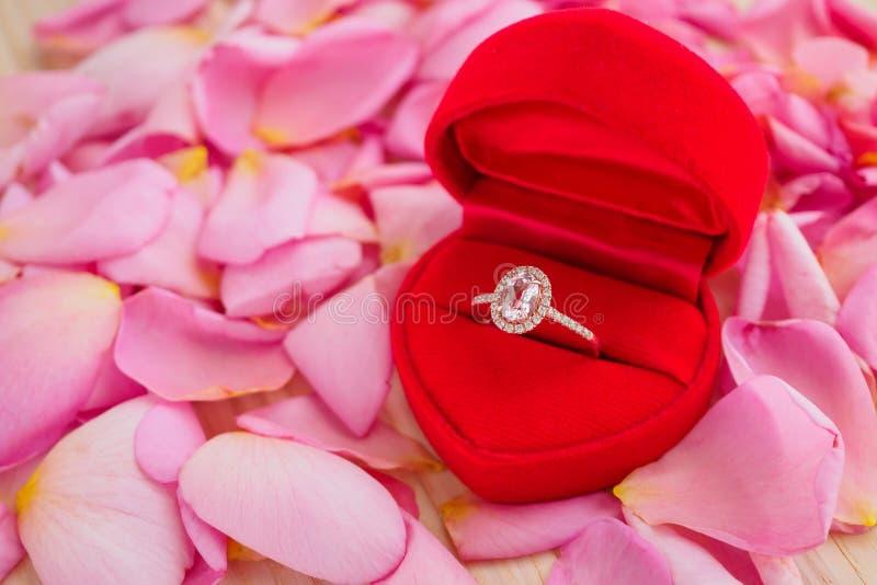 Элегантное кольцо с бриллиантом свадьбы в шкатулке для драгоценностей сердца на красивой розовой предпосылке лепестка розы стоковое изображение