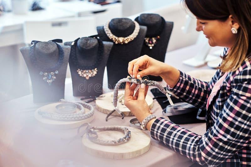 Элегантно одетая женщина делает handmade ожерелья, работающ с иглами и потоком в мастерской стоковые изображения
