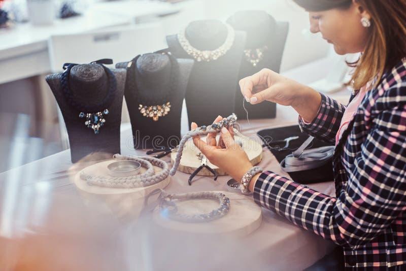 Элегантно одетая женщина делает handmade ожерелья, работающ с иглами и потоком в мастерской стоковая фотография