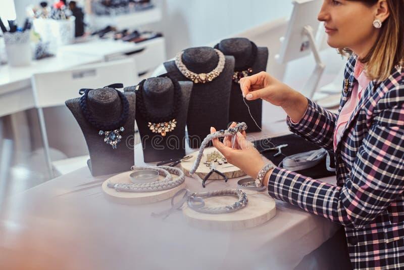 Элегантно одетая женщина делает handmade ожерелья, работающ с иглами и потоком в мастерской стоковое изображение rf