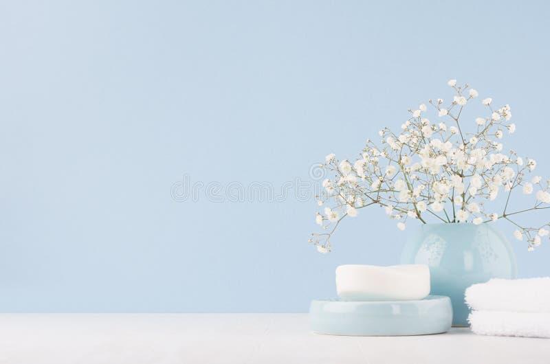 Элегантные аксессуары для таблицы шлихты - мягко пастельные голубые керамические шары, белые цветки, продукты для кожи и тело заб стоковые фотографии rf