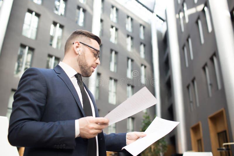 Элегантные бумаги чтения человека на улице стоковое фото