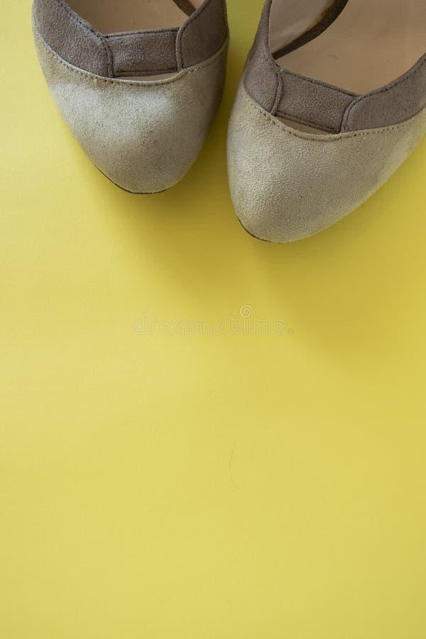 Элегантные женские ботинки на желтой предпосылке, космосе для текста o Минимальная концепция моды стоковое изображение