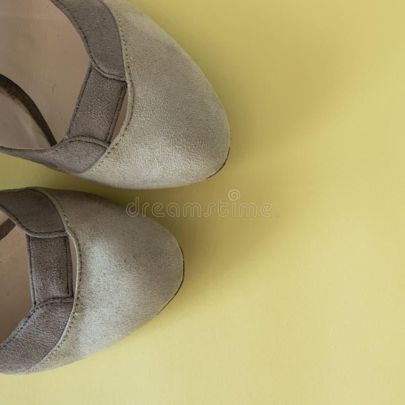 Элегантные женские ботинки на желтой предпосылке, космосе для текста o Минимальная концепция моды стоковые фотографии rf