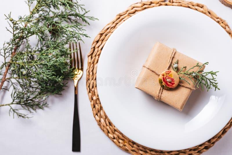 Элегантные настройки места для Рождества, подарочная коробка на блюде сверху стоковые изображения