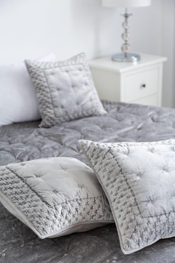 Элегантные серые подушки на кровати в минимальном интерьере спальни гостиницы при включении лампа белый шкаф Реальное фото стоковая фотография rf