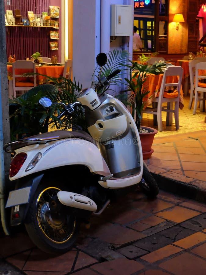 Элегантный белый скутер припаркованный около кафа, nighttime стоковое фото rf