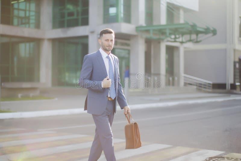 Элегантный бизнесмен в голубом костюме идя из банка стоковые изображения rf