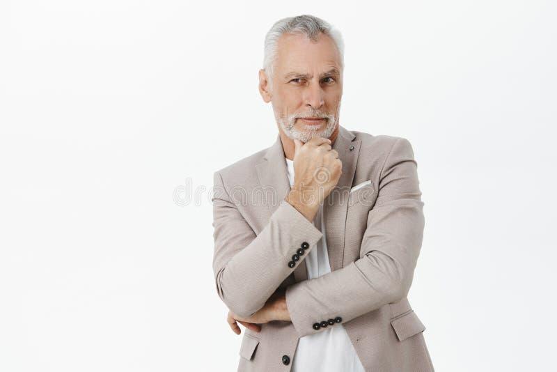 Элегантный красивый и харизматический мужчина в костюме с серыми волосами и морщинками держа руку на подбородке во внимательном ж стоковая фотография