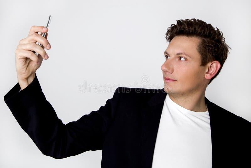 Элегантный, молодой человек в костюме, стоя на белой предпосылке и стоковые фото