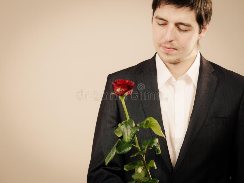 Элегантный молодой человек с красной розой стоковые фотографии rf