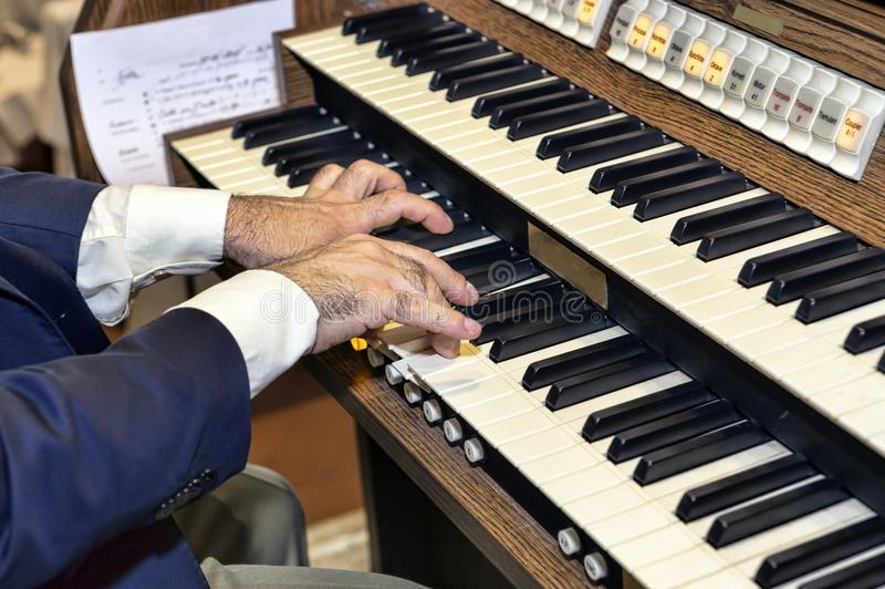 Элегантный музыкант играет орган стоковая фотография
