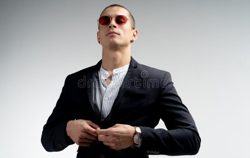 Элегантный уверенный молодой бизнесмен с короткой стрижкой в красных солнечных очках нося черный костюм изолированный над белизно стоковое изображение rf