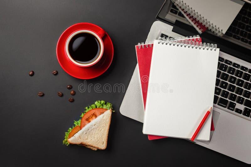 Элегантный черный рабочий стол офиса с ноутбуком, чашкой кофе и сэндвичем на обед стоковые фотографии rf