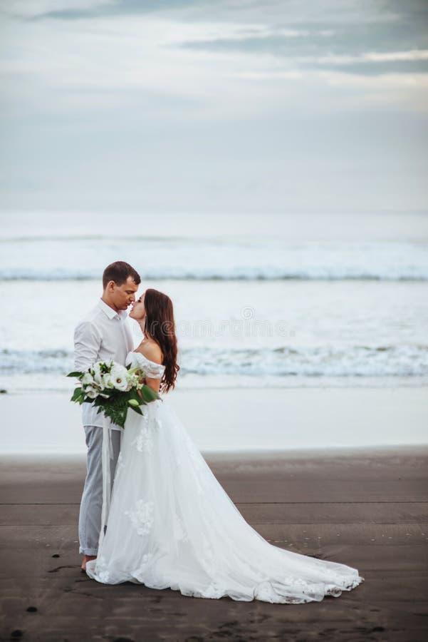 Элегантный шикарный жених и невеста идя на пляж океана во время времени захода солнца стоковые фото