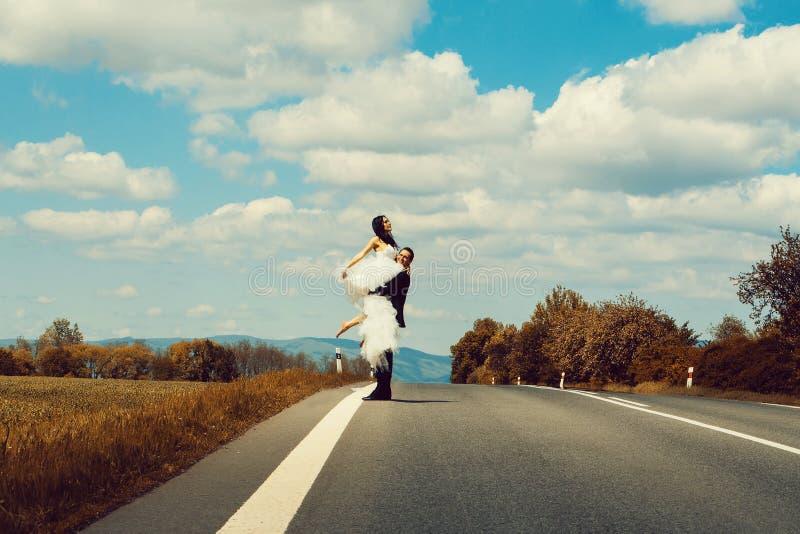 Элегантный groom держит красивую невесту стоковые фото