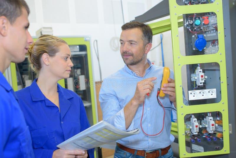 Электрики проверяя напряжение тока в частично установленном электрическом гнезде стоковая фотография rf