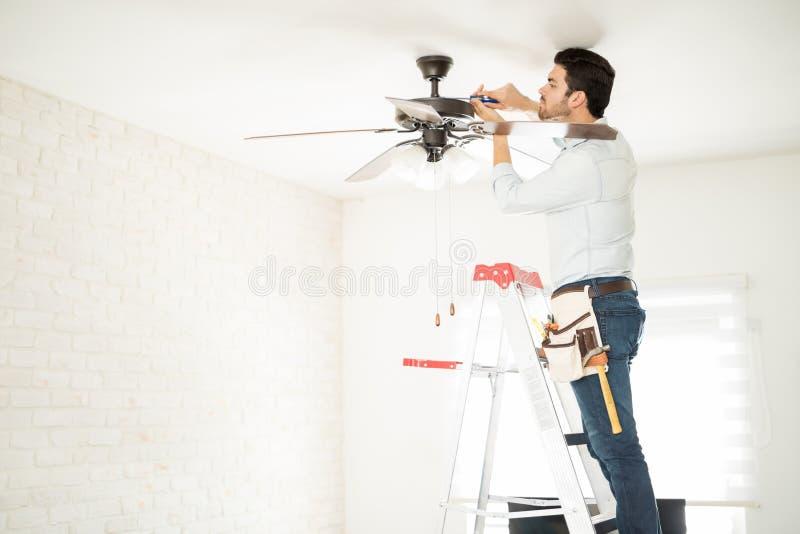 Электрик исправляя потолочный вентилятор стоковая фотография rf