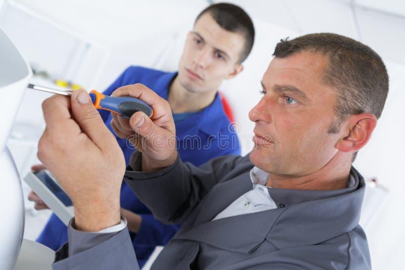 Электрик и мужчина apprentice учить использовать отвертку стоковые изображения