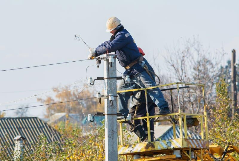 Электрик на кране работая с высоковольтными проводами стоковая фотография rf