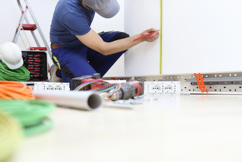 Электрик на работе с измерениями карандаша и метра на стене положение для электрического гнезда, устанавливает электрические конт стоковая фотография