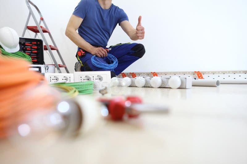 Электрик на работе с острозубцами и проводами в руке, показывает большой палец руки как, устанавливает лампы дома, электрические  стоковые изображения rf