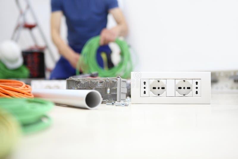 Электрик на работе с пачкой кабеля в руке, устанавливает гнездо, электрические контуры, электрическую проводку стоковые изображения rf
