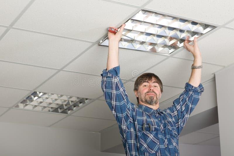 электрик потолка устанавливает освещение к стоковая фотография