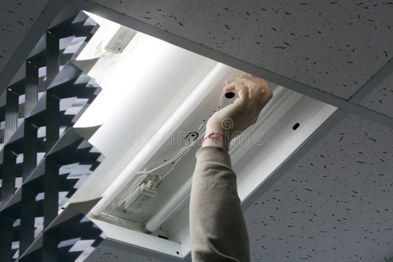 Электрик пришел к офису проверить и отремонтировать свет стоковое фото