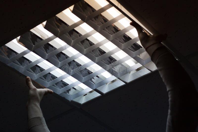 Электрик пришел к офису проверить и отремонтировать свет стоковые изображения