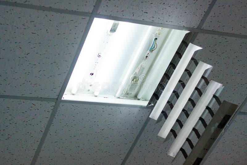 Электрик пришел к офису проверить и отремонтировать свет стоковые фотографии rf
