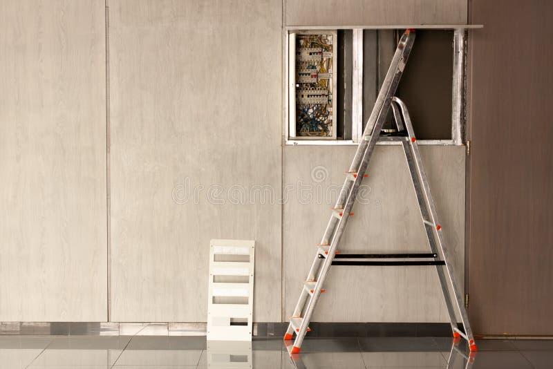 Электрик пришел к размерам офиса отремонтировать электричество в комнате Используемый stepladder для ремонта стоковое фото rf