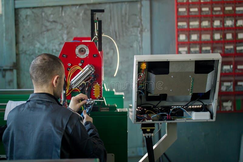 Электрик работника человека работает с панелью энергии и оборудованием машинного оборудования на заводе стоковое фото rf